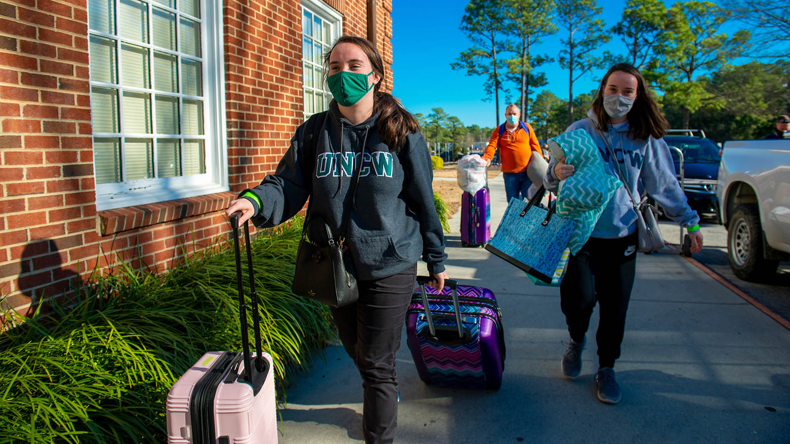 Bringing bags and rolling suitcases, twin sisters Molly (left) and Jenny (right) Norris walk with their luggage to their residence hall. A man follows carrying bags and bedding.