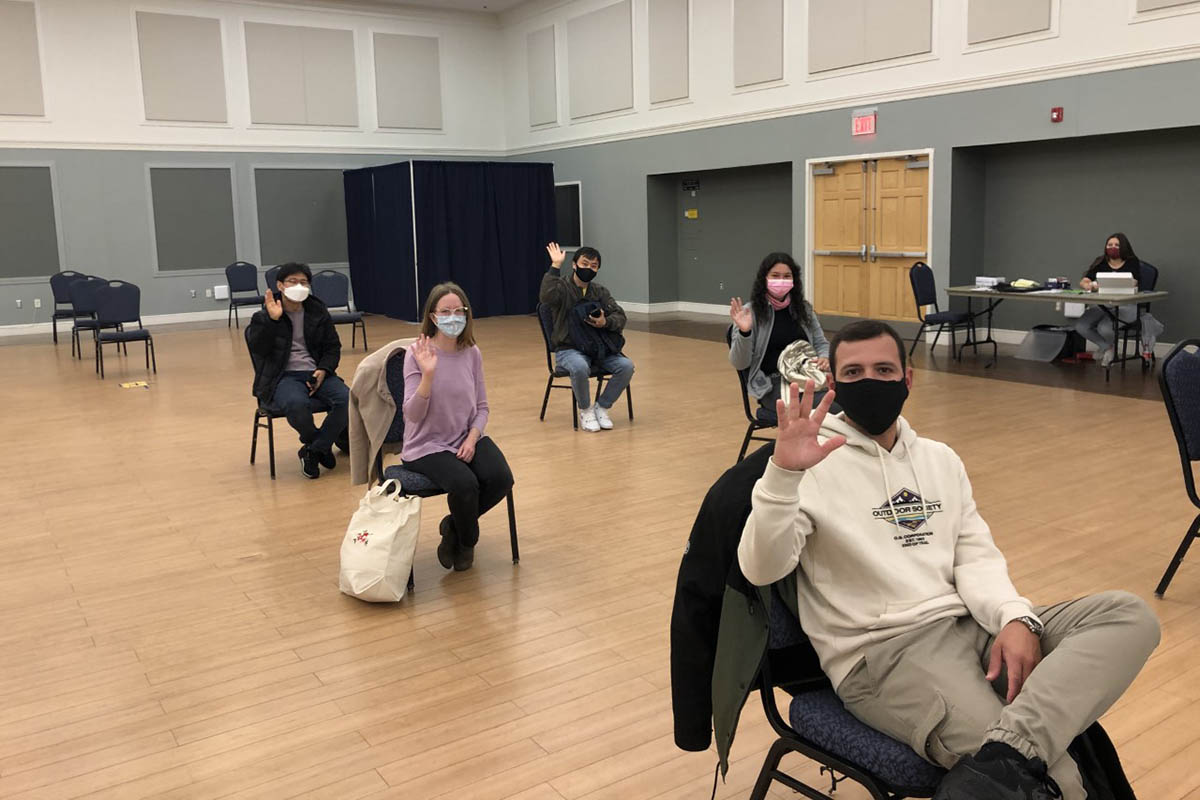 Students from multiple countries, wearing masks and seated to support social distancing, attend orientation for a program to help them improve their English language skills.