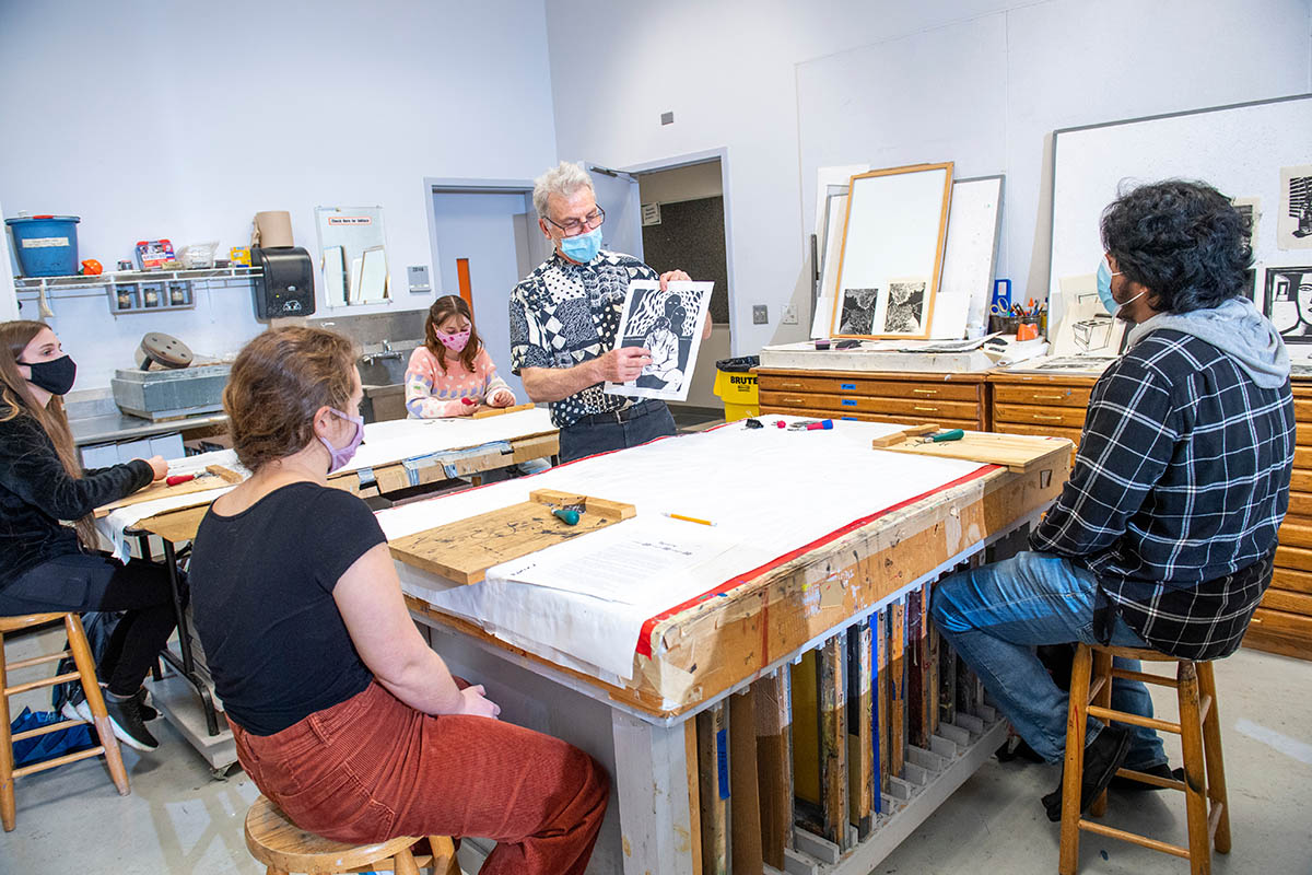 Donald Furst (standing) holds a print while four students look on or work on their own prints.