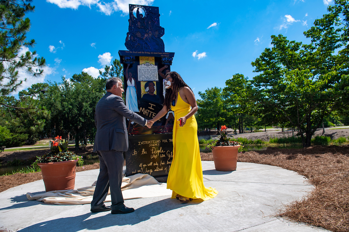 """Chancellor Sartarelli (left) shakes hands with artist Dare Coulter in front of her artwork, titled """"Because It's Time,"""" encapsulating the joy and pain of the Black experience in Wilmington."""