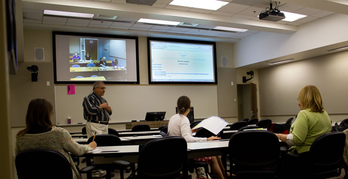 professor lecturing in a video teleconferencing classroom