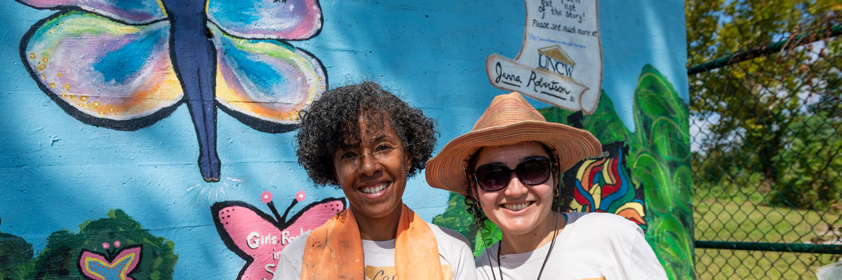 Watson College of Education faculty Candace Thompson and Daisy Barreto chip in with red paint as  UNCW faculty, staff and students combine their efforts to help with landscape efforts at DREAMS of Wilmington non-profit child advocacy program during WingsUp for Wilmington, a Day of Seahawk Service