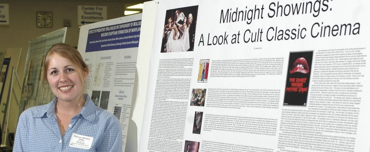 student standing next to poster presentation