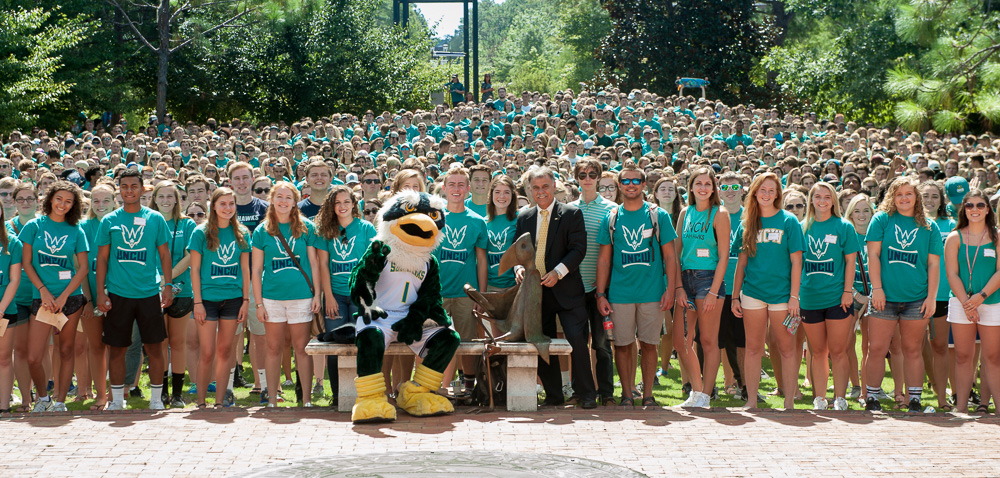 Chancellor Sartarelli and Sammy Seahawk surrounded by incoming students dressed in teal at convocation