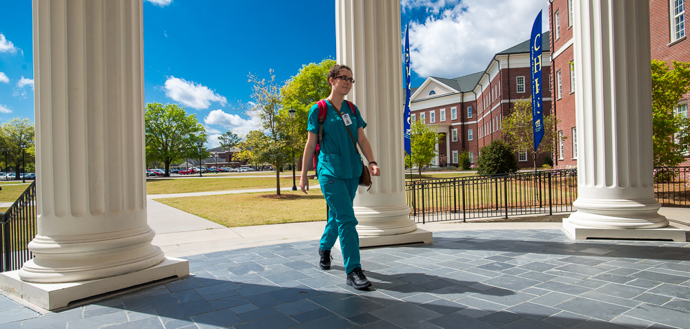 Student in scrubs walking on campus