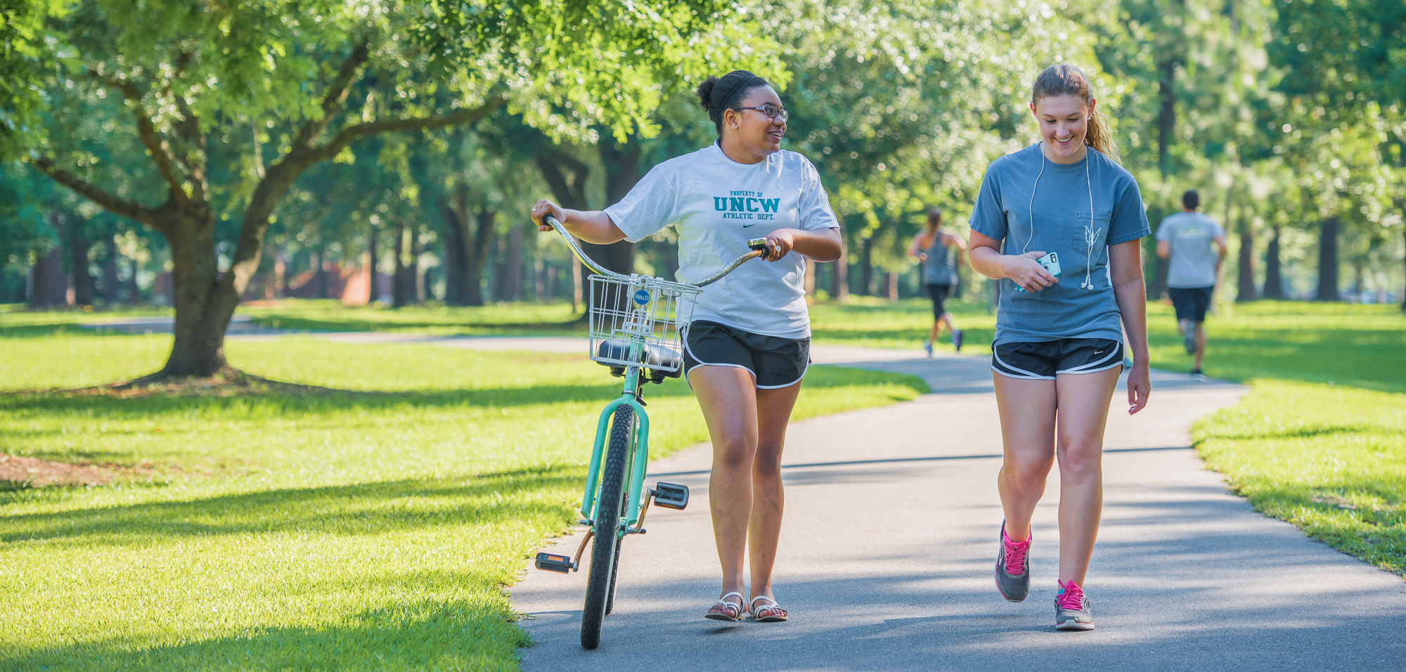 Two female students walking bikes on campus