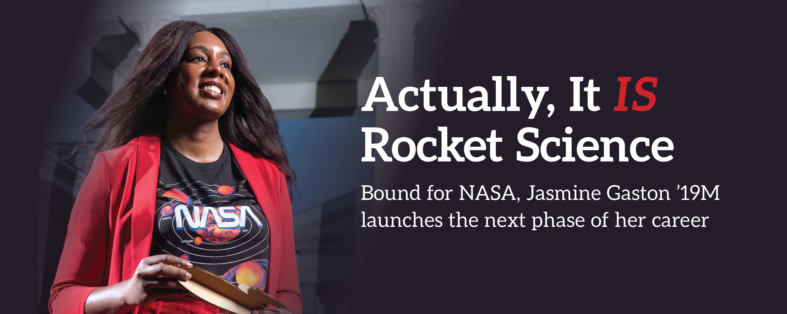 Jasmine Gaston in a NASA tshirt and a red suit holding a cardboard rocket