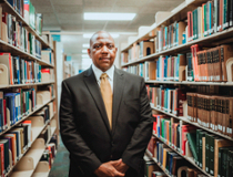 Dr. Jimmy T. Tate standing in a library surrounded by books