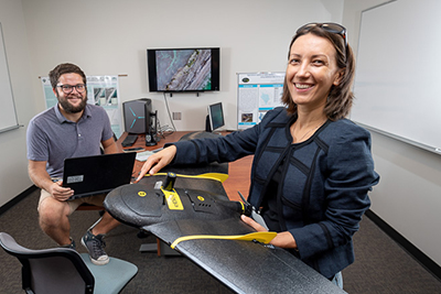 Narcisa Pricope, right, and Britton Baxley '19M, left, with a drone that will map coastal changes.