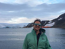 Doctoral student Katie Reed '21Ph.D. stands surrounded by water and snow-covered terrain in Antarctica.