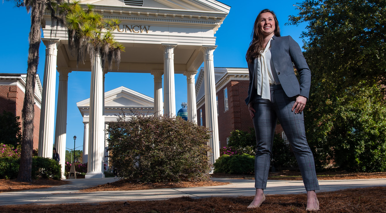 Woman in suit smiling by columns with UNCW in background