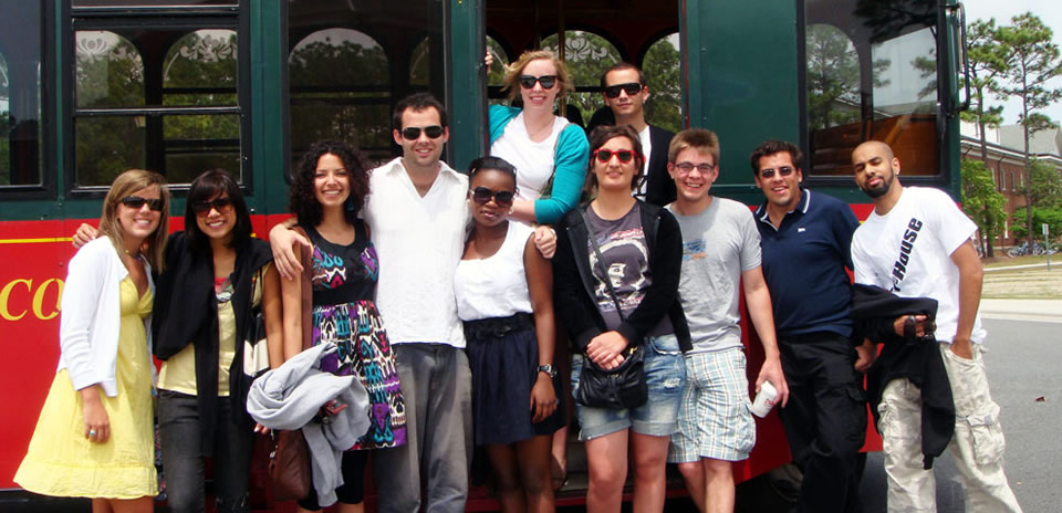 Study abroad ambassadors and international students in front of trolly