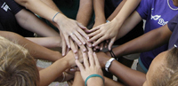 Students hands join together in a circle.