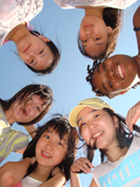 Students standing in a cirlce looking down at the camera.
