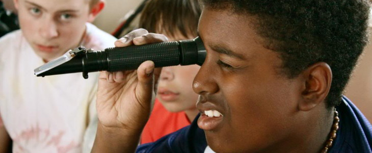 boy looking through a refractometer