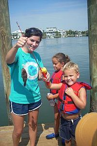 marinequest staff with student holding up fish on pole