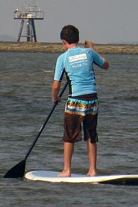 UNCW MarineQuest summer surf camp boy on standup paddleboard
