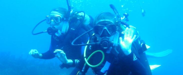 female scuba divers waving at camera