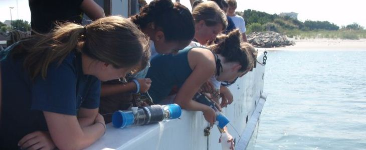 students working over the edge of research boat