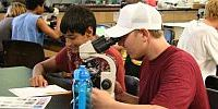 MarineQuest summer camp boy participants using microscopes