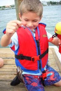 young boy with a fish on his hook at a dock