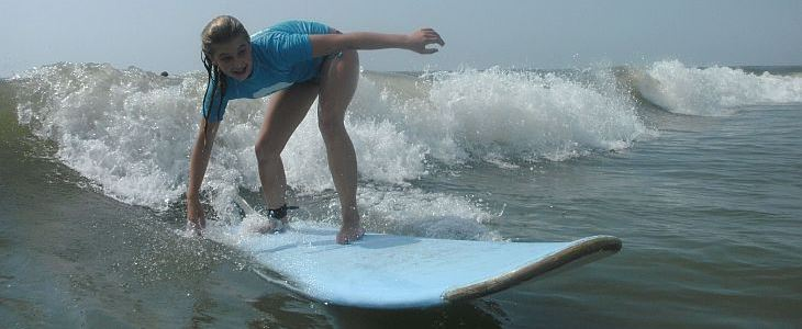 young girl surfing with MarineQuest surfing summer camp program