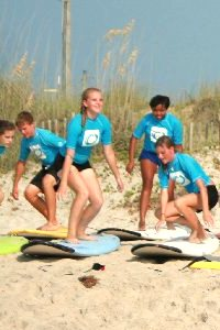 teenagers learning to surf on the beach