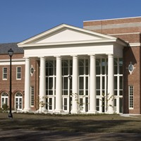 brick building with white columns in front