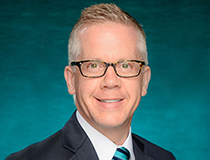 Michael Wilhelm official portrait with a teal background