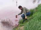 Larry Cahoon sampling hog waste from a waste lagoon