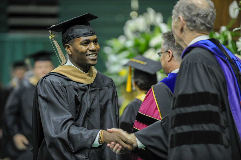 graduate student congratulatory handshake during commencement