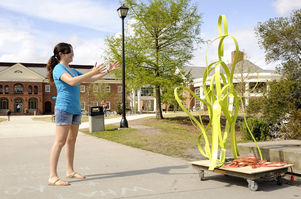 student admiring her abstract art displayed on campus grounds